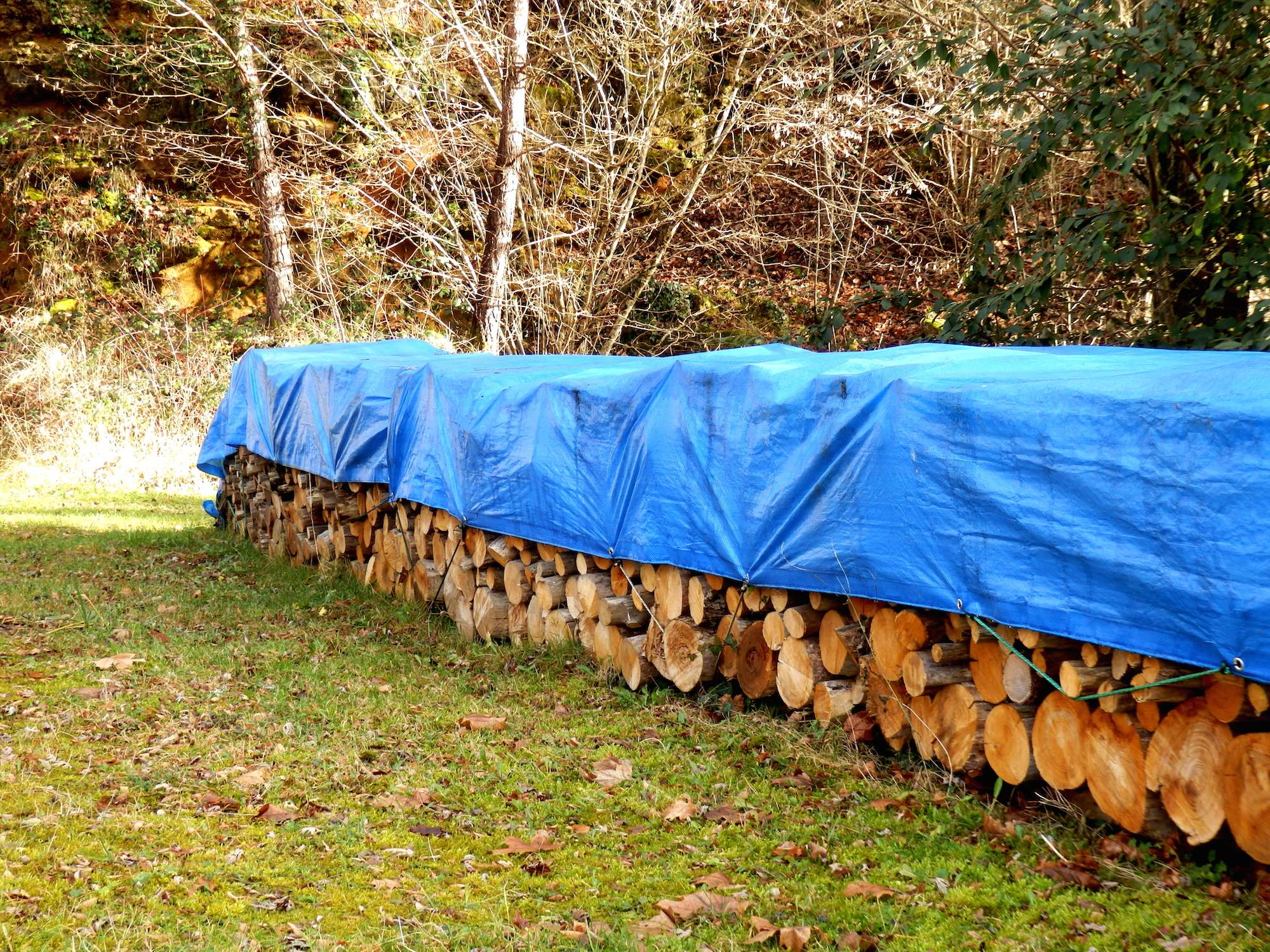 A Blue tarpaulin being used to protect and cover wood by Yuzet®.
