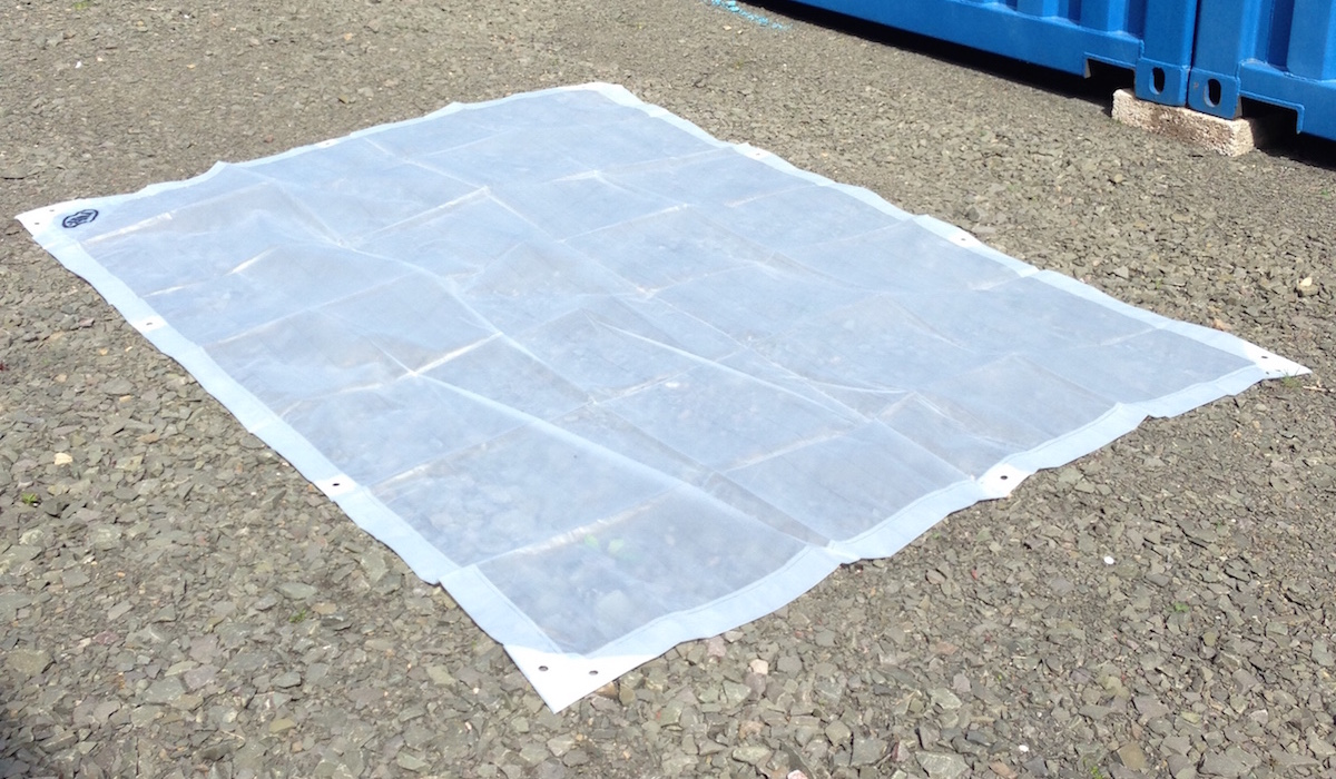 Clear tarpaulin layed out on gravel..